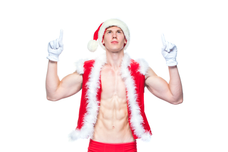 Sexy Santa Claus pointing in white blank sign. Young muscular man wearing Santa Claus hat demonstrate his muscles. Isolated on white background.