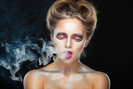 Halloween. Portrait of young beautiful girl with make-up. E-cigarette smoke, Viper. Isolated on black background. 写真素材