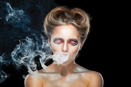 Electronic cigarette wiper. Halloween. Portrait of young beautiful girl with make-up. E-cigarette smoke, Viper. Isolated on black background.