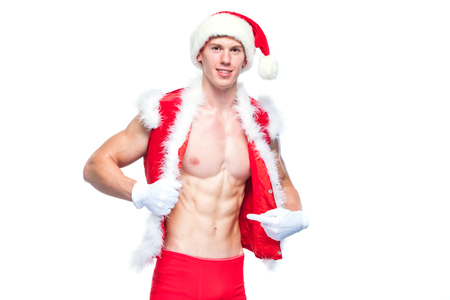 Sexy Santa Claus . Young muscular man wearing Santa Claus hat demonstrate his muscles. Isolated on white background.