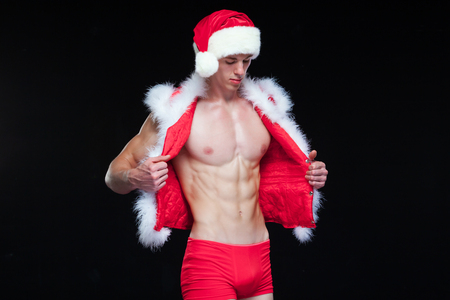 Sexy Santa Claus . Young muscular man wearing Santa Claus hat demonstrate his muscles. Isolated on black background. Stock Photo