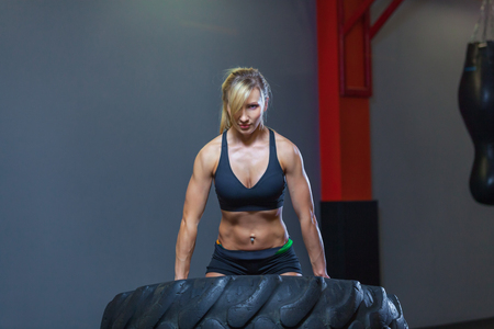 Fit female athlete working out with a huge tire, turning and carry in the gym. Crossfit woman exercising with big tire