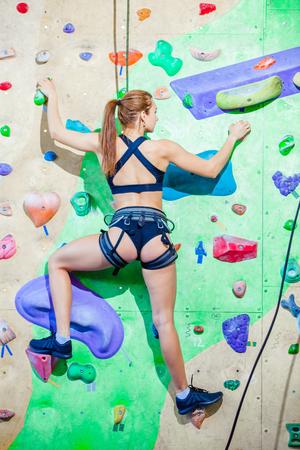 Frau, die an einer Wand in einem Kletterzentrum im Freien klettert