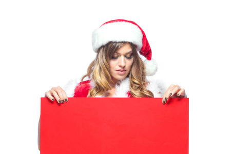 Christmas. Beautiful muscular sexual happy woman in Santa Claus clothes. Keeps blank whiteboard. Isolated on white background.