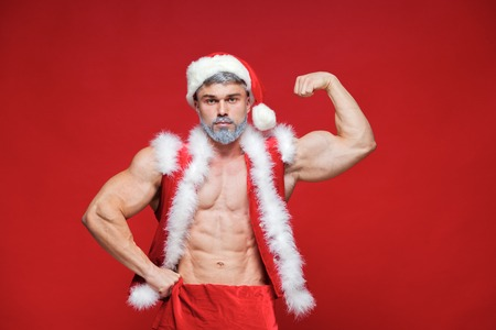 Christmas. Sport, activity. Sexy Santa Claus . Young muscular ma