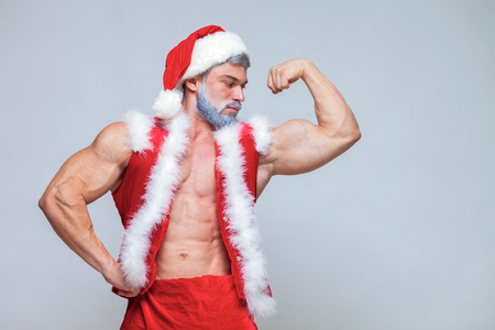 Christmas. Sexy Santa Claus . Young muscular man wearing Santa C