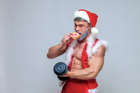 Muscular man in santa costume lifting dumbbell while eating a donut