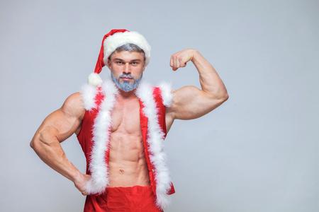 Christmas. Sexy Santa Claus . Young muscular man wearing Santa C