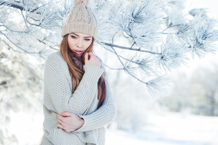 Beautiful winter portrait of young woman in the snowy scenery 写真素材