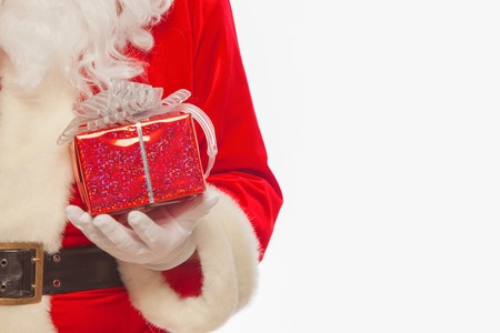 Photo of Santa Claus gloved hands holding red giftbox, isolated