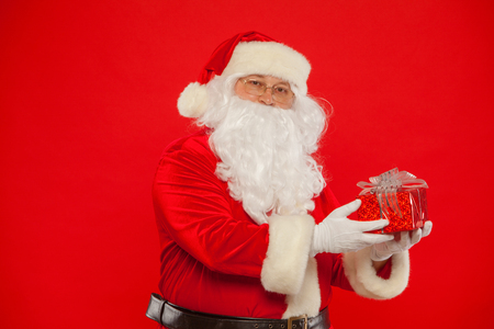 Photo of Santa Claus gloved hand with giftbox, on a red backgrou Stock Photo