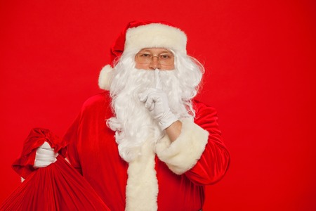Portrait of Santa Claus with huge red sack keeping forefinger by
