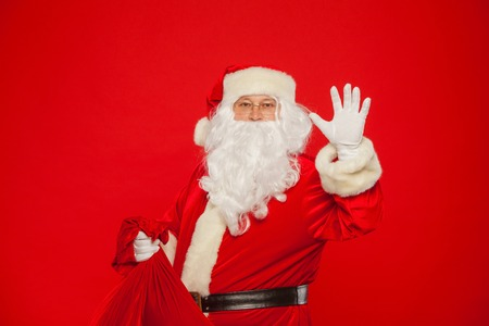 Portrait of Santa Claus with huge red sack hand up looking at ca