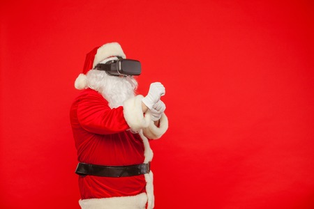 Santa Claus wearing virtual reality goggles, on a red background Stock Photo