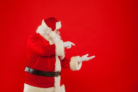 Santa Claus pointing in blank a place, red background Stock Photo