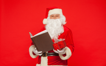Santa Claus reads old book, on a red background. Christmas