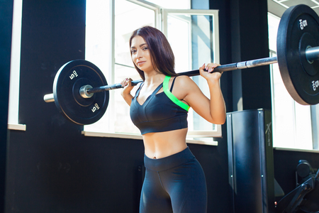 Young fit girl doing heavy duty squats in gym with barbell in beautiful sportswear