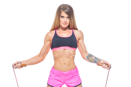 Attractive, sexy, muscular girl in pink shorts and a black top jumps over a modern rope with wooden handles. Cardio-training. Fitness, healthy lifestyle concept. Isolated on the white background.