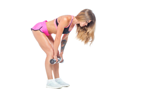 Attractive, sexy, muscular girl in pink shorts and black top makes slopes with dumbbells of steel color. Dead lift. Fitness, healthy lifestyle concept. Isolated on the white background.