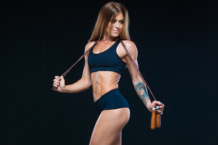 Muscular and sexy girl with long hair in black clothes with a modern rope with wooden handles. Fitness, healthy lifestyle concept. Isolated on the black background.