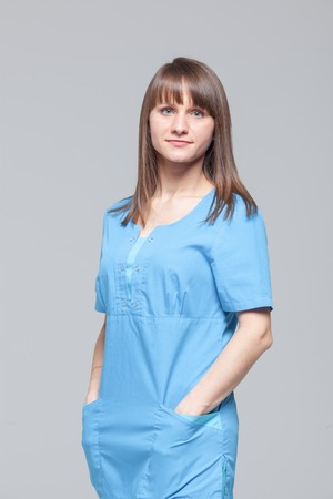 Portrait of young female doctor standing in blue uniform Stock Photo