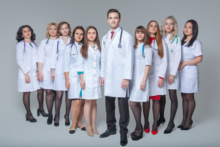 Full length portrait of an attractive male doctor staying at the head of group of doctors Фото со стока - 124794100