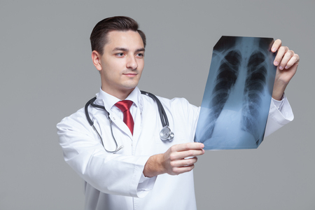 Young male doctor looking at the x-ray picture of lungs Фото со стока - 124794108