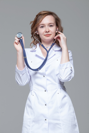 Female doctor with stethoscope standing and looking at camera