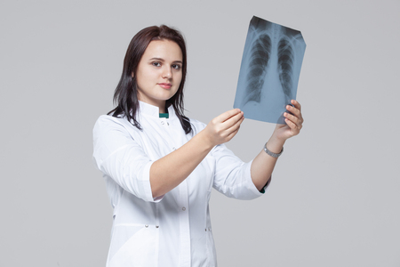 Young female doctor looking at the x-ray picture of lungs 写真素材