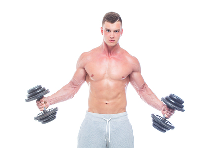 Handsome power athletic man with dumbbell confidently looking forward. Strong bodybuilder with six pack, perfect abs, shoulders, biceps, triceps and chest. Strong Athletic Man - Fitness Model showing his perfect body isolated on white background with copyspace Фото со стока