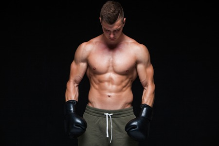 Muscular young man in black boxing gloves and shorts shows the different movements and strikes in the studio on a dark background. Strong Athletic Man - Fitness Model showing his perfect body. Copy Space.
