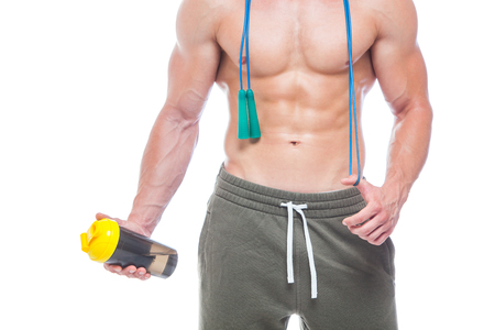 Muscular man skipping rope. Portrait of muscular young man with jumping rope drinking water with over neck, isolated on white background. Strong Athletic Man - Fitness Model showing his perfect body.