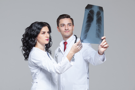 Two young doctors looking at the x-ray picture of lungs