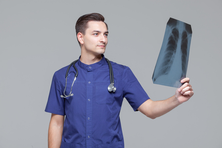 Young male doctor studying the x-ray picture of lungs