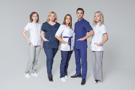 Successful team of medical doctors are looking at camera while standing on grey background