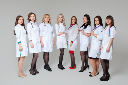Full length portrait of a successful group of doctors staying in front of grey background Фото со стока - 124795174