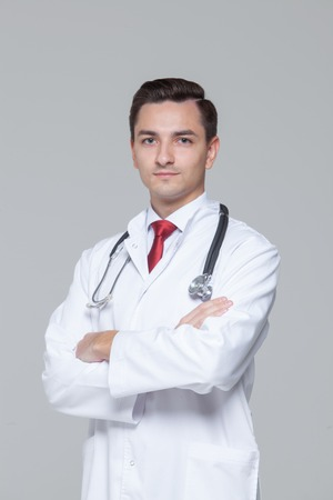 Male doctor with stethoscope standing and looking at camera Фото со стока