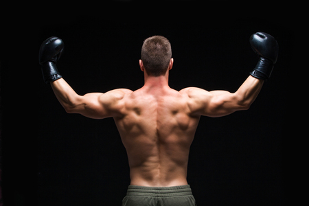 Powerful back. Muscular young man in black boxing gloves and shorts shows the different movements and strikes in the studio on a dark background. Strong Athletic Man - Fitness Model showing his perfect body. Copy Space.
