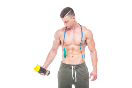 Muscular man skipping rope. Portrait of muscular young man with jumping rope drinking water with over neck, isolated on white background. Strong Athletic Man - Fitness Model showing his perfect body Stock Photo