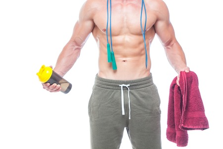 Muscular man skipping rope. Portrait of muscular young man with jumping rope drinking water with red towel over neck, isolated on white background. Strong Athletic Man - Fitness Model showing his perfect body Фото со стока - 124795182