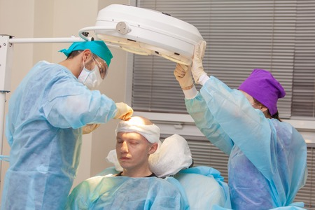 The surgeon directs the lamp light. Baldness treatment. Hair transplant. Surgeons in the operating room carry out hair transplant surgery. Surgical technique that moves hair follicles from a part of the head.