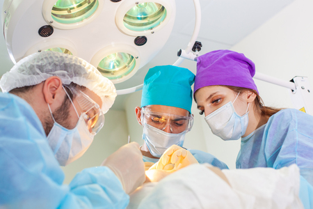 Baldness treatment. Hair transplant. Surgeons in the operating room carry out hair transplant surgery. Surgical technique that moves hair follicles from a part of the head. Reklamní fotografie