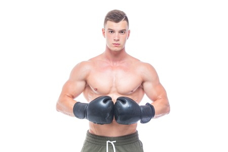 Muscular young man in black boxing gloves and shorts shows the different movements and strikes in the studio on a white background. Strong Athletic Man - Fitness Model showing his perfect body. Copy Space. Фото со стока - 124791733