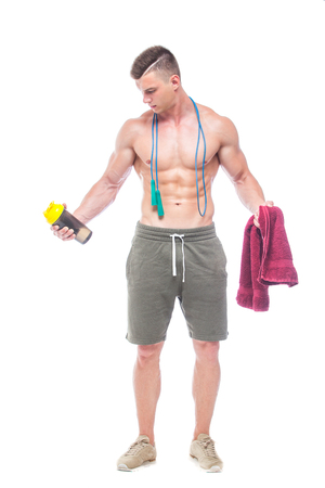 Muscular man skipping rope. Portrait of muscular young man with jumping rope drinking water with red towel over neck, isolated on white background. Strong Athletic Man - Fitness Model showing his perfect body.