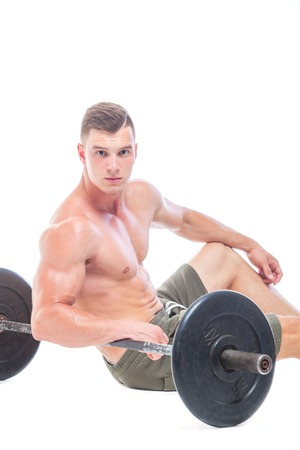 Muscular man working out in studio doing exercises with barbell at biceps, strong male naked torso abs. Isolated on white background. Copy Space. Rest, Sits on the floor at the barbell. Fatigue.