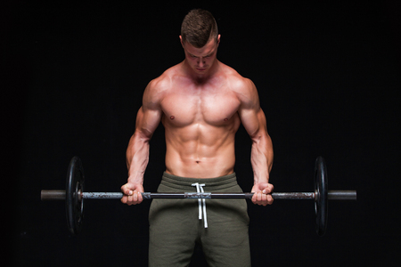 Muscular man working out in studio doing exercises with barbell at biceps, strong male naked torso abs. Isolated on black background. Copy Space. Strong tension. Sweat. Scream. Фото со стока - 124795223