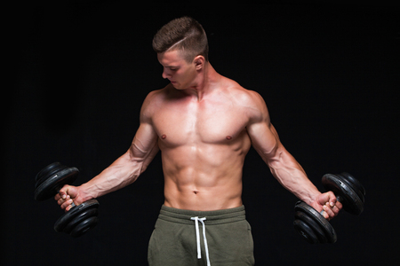 Handsome power athletic man with dumbbell confidently looking forward. Strong bodybuilder with six pack, perfect abs, shoulders, biceps, triceps and chest. Strong Athletic Man - Fitness Model showing his perfect body isolated on black background with copyspace