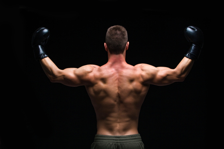 Powerful back. Muscular young man in black boxing gloves and shorts shows the different movements and strikes in the studio on a dark background. Strong Athletic Man - Fitness Model showing his perfect body. Copy Space. Фото со стока - 124795226