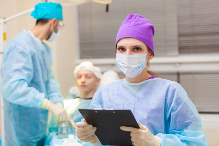 Beautiful portrait of a doctor with documents on the background of the operating room. Baldness treatment. Hair transplant. Surgeons in the operating room carry out hair transplant surgery. Surgical technique that moves hair follicles from a part of the head. Фото со стока - 124791759