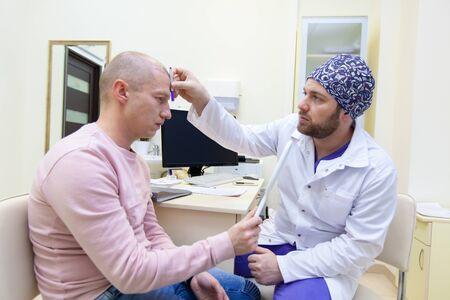 Baldness treatment. Patient suffering from hair loss in consultation with a doctor. Preparation for hair transplant surgery. The line marking the growth of hair. The patient controls the marking in the mirror Фото со стока - 124791765